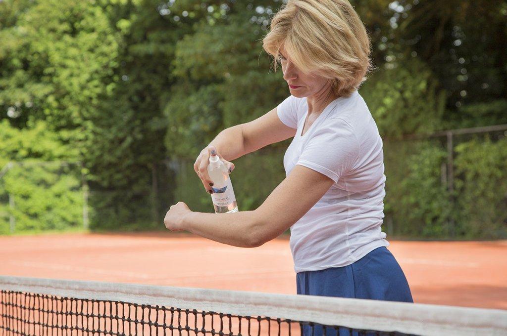vrouw sprayt permsal magnesium tijdens het tennissen