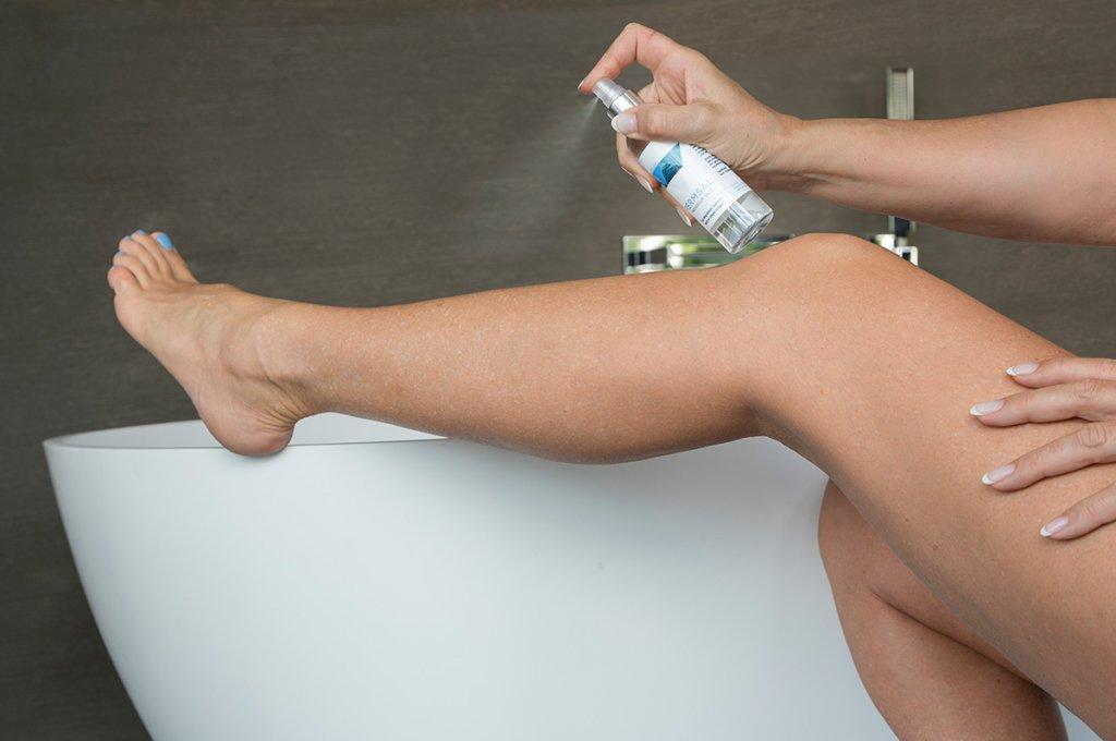 sprayen van permsal magnesium op het been zittend bij een bad