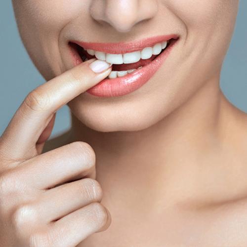 dame met witte tanden en de wijsvinger in de mond